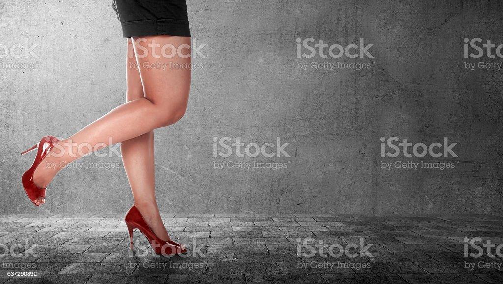 Beautiful female legs wearing high heels in black dress stock photo