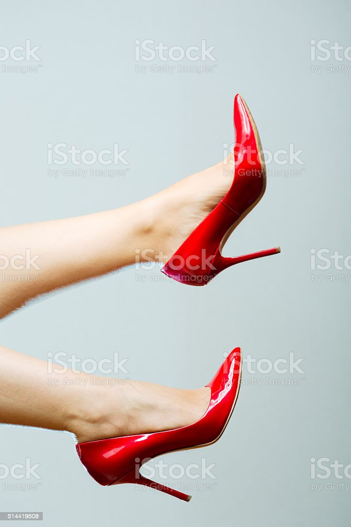 Beautiful female legs with red heels stock photo