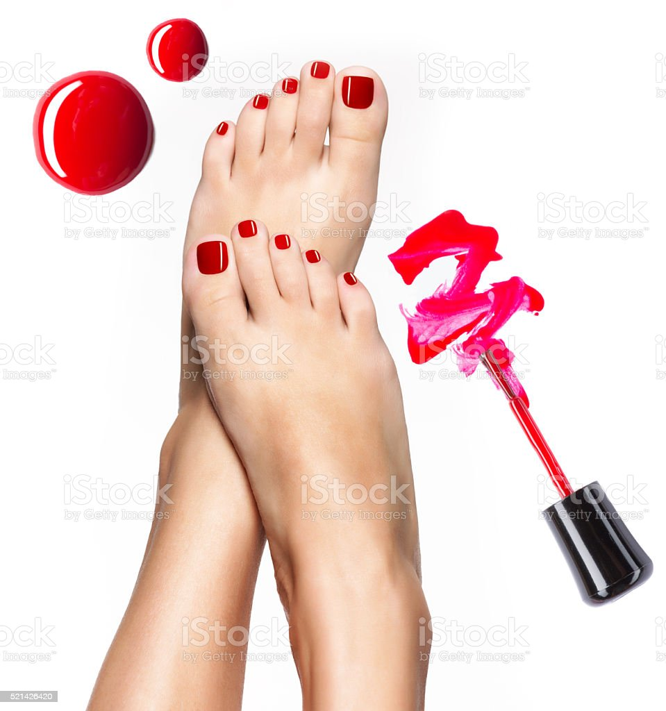 Beautiful female legs with red pedicure and  nail polish stock photo