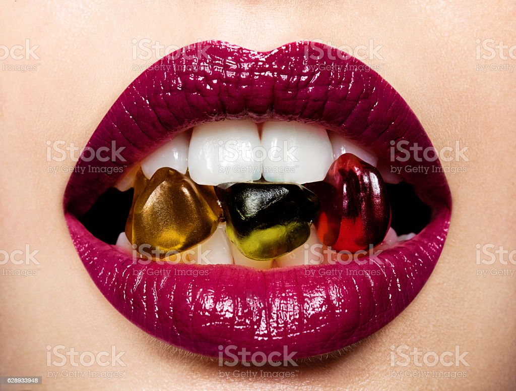 Beautiful female lips with gummi bears stock photo
