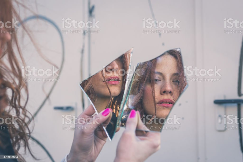 A beautiful female looking at herself in broken mirror piece stock photo