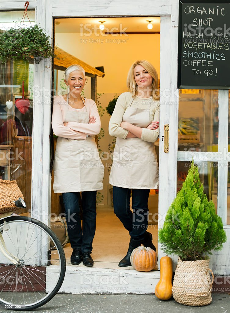 Beautiful female owner's holding standing in front of their shop stock photo