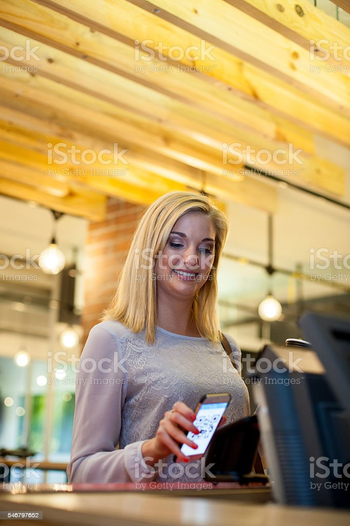 Beautiful female pays using her smart phone stock photo