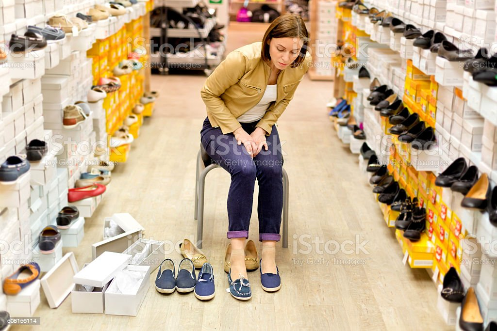 Beautiful female shopping for shoes stock photo