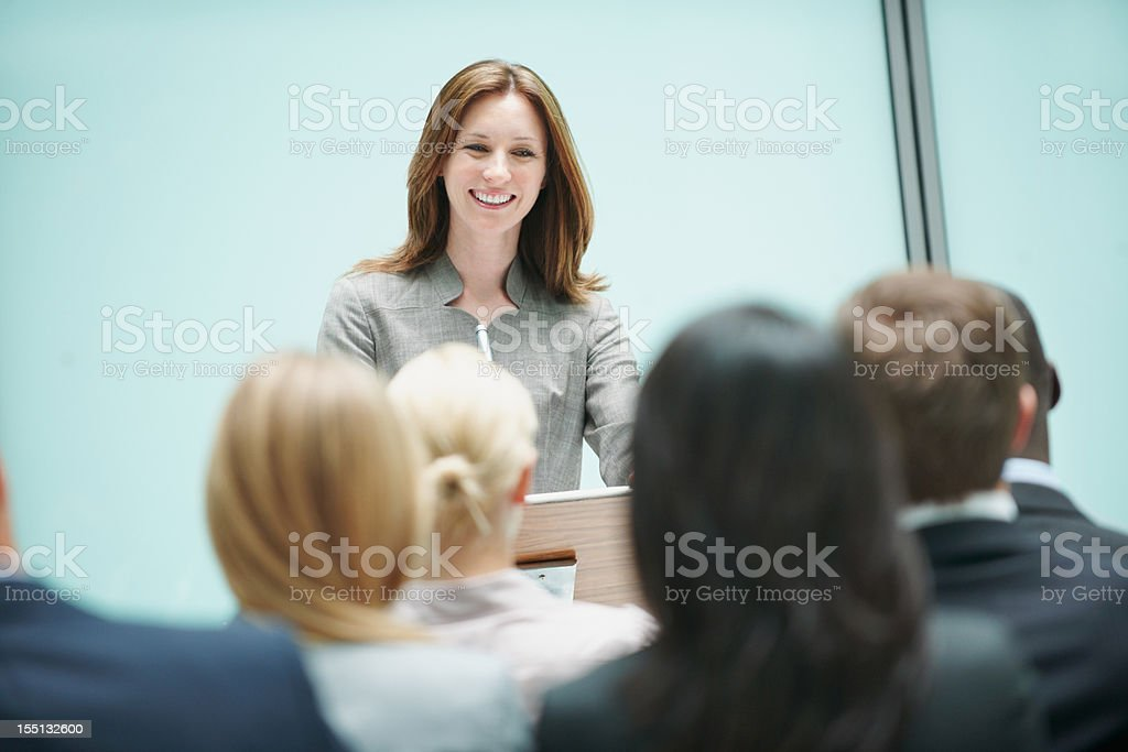 Beautiful female speaker speaking at a conference stock photo