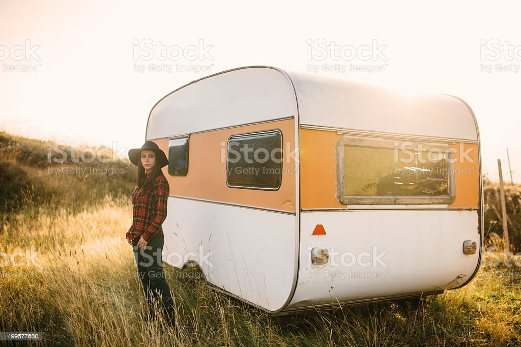 Beautiful female standing next to the car trailer stock photo