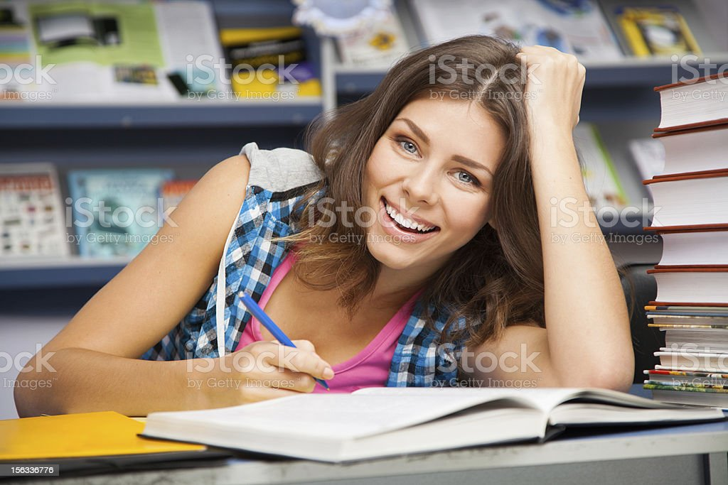 Beautiful female student in a library royalty-free stock photo