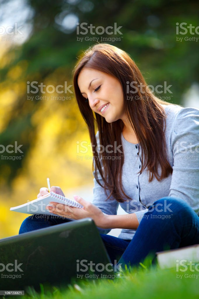 Beautiful female student learning in park royalty-free stock photo