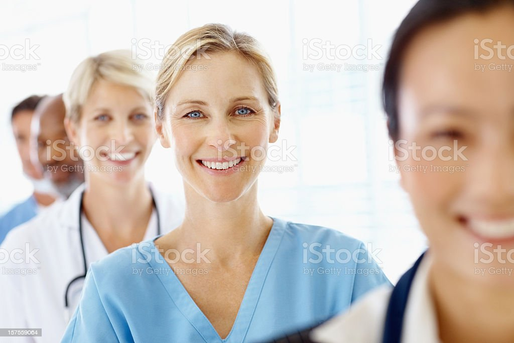 Beautiful female surgeon smiling between her co-workers royalty-free stock photo