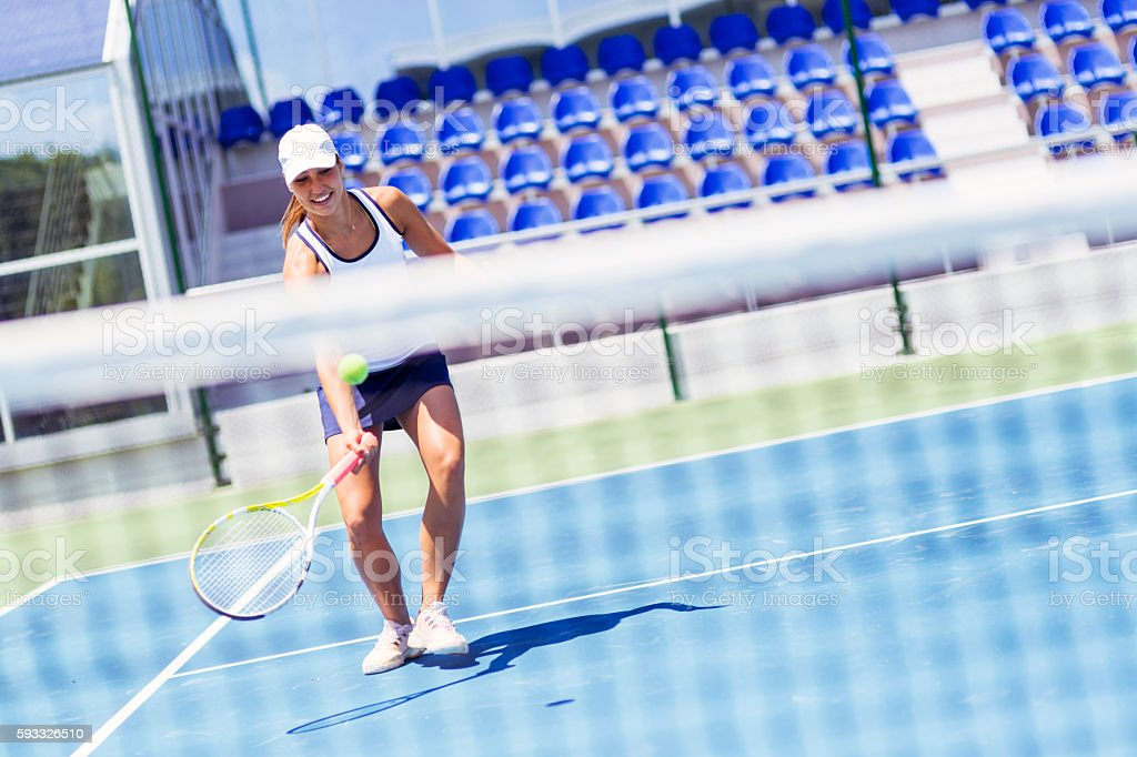 Beautiful female tennis player in action stock photo