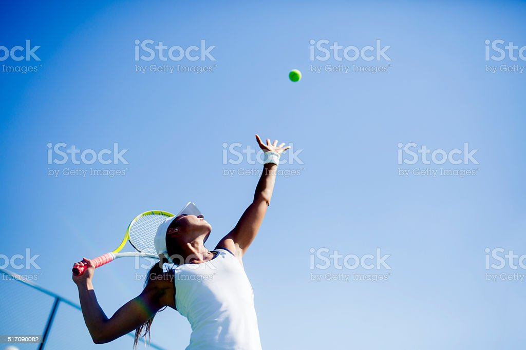 Beautiful female tennis player serving royalty-free stock photo