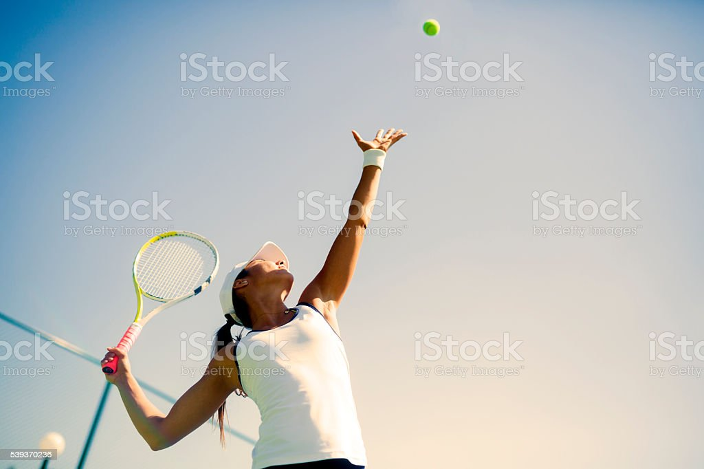 Beautiful female tennis player serving stock photo