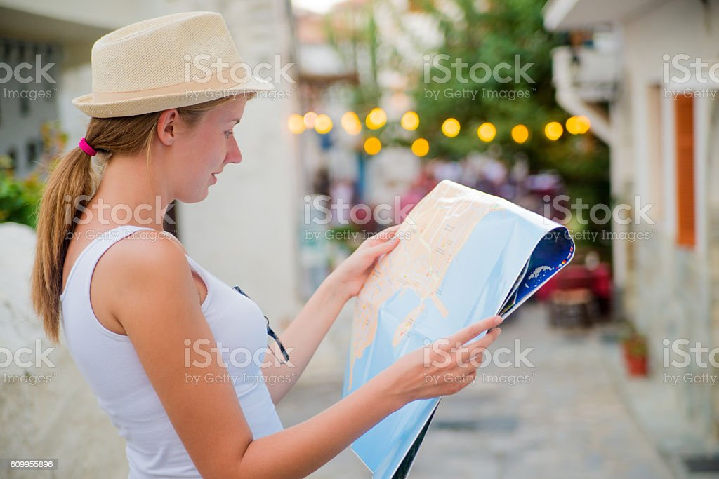 beautiful female tourist searching a place on the map stock photo