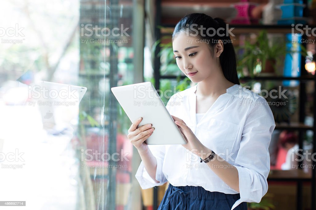 beautiful female using digital tablet in cafe stock photo