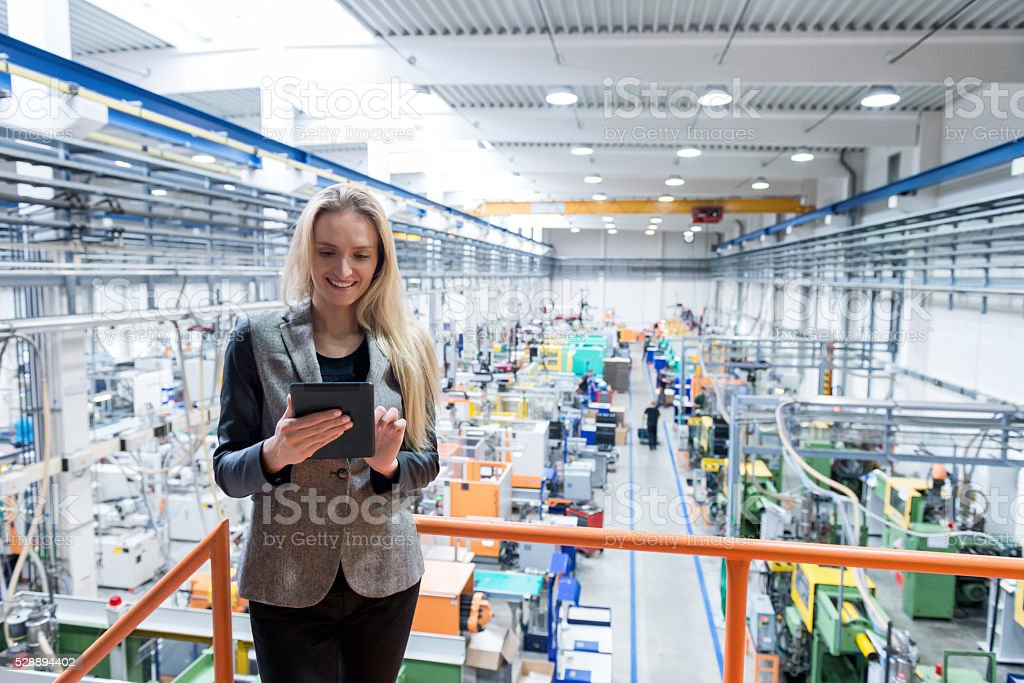 Beautiful female worker working on digital tablet stock photo