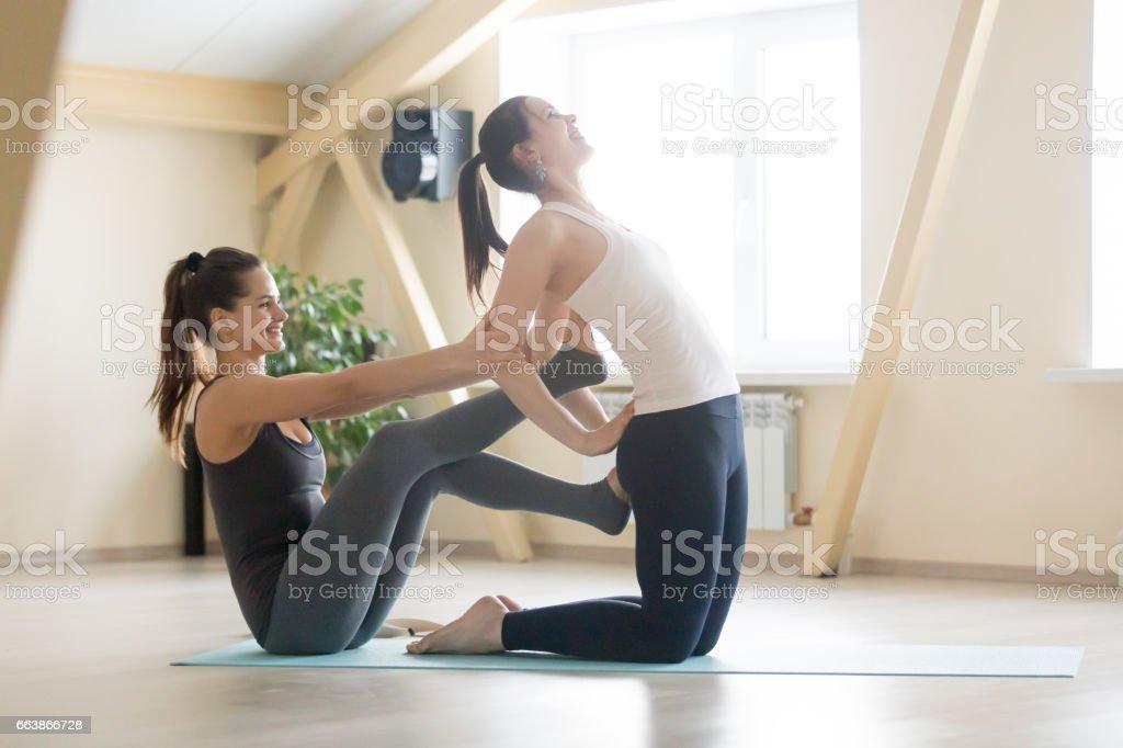 Beautiful female yogi trainer teaching young woman in yoga class stock photo