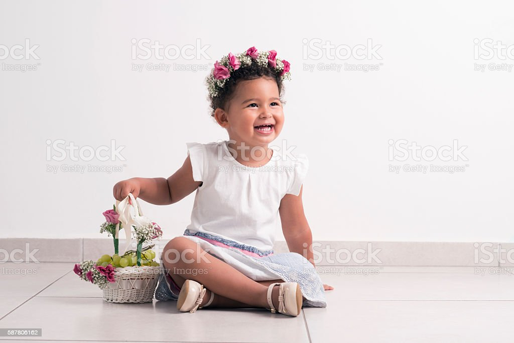 Beautiful festive girl with basket sitting on floor. stock photo