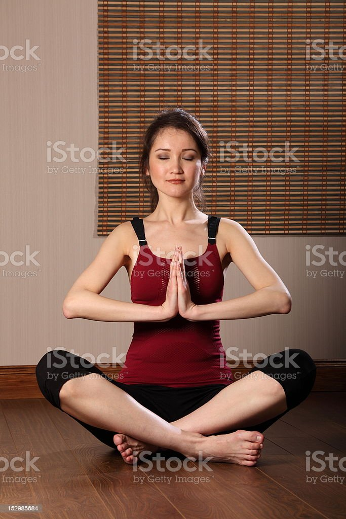 Beautiful fit young oriental woman meditating eyes closed royalty-free stock photo