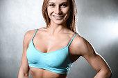 beautiful fitness model posing in studio on white grey backgroun
