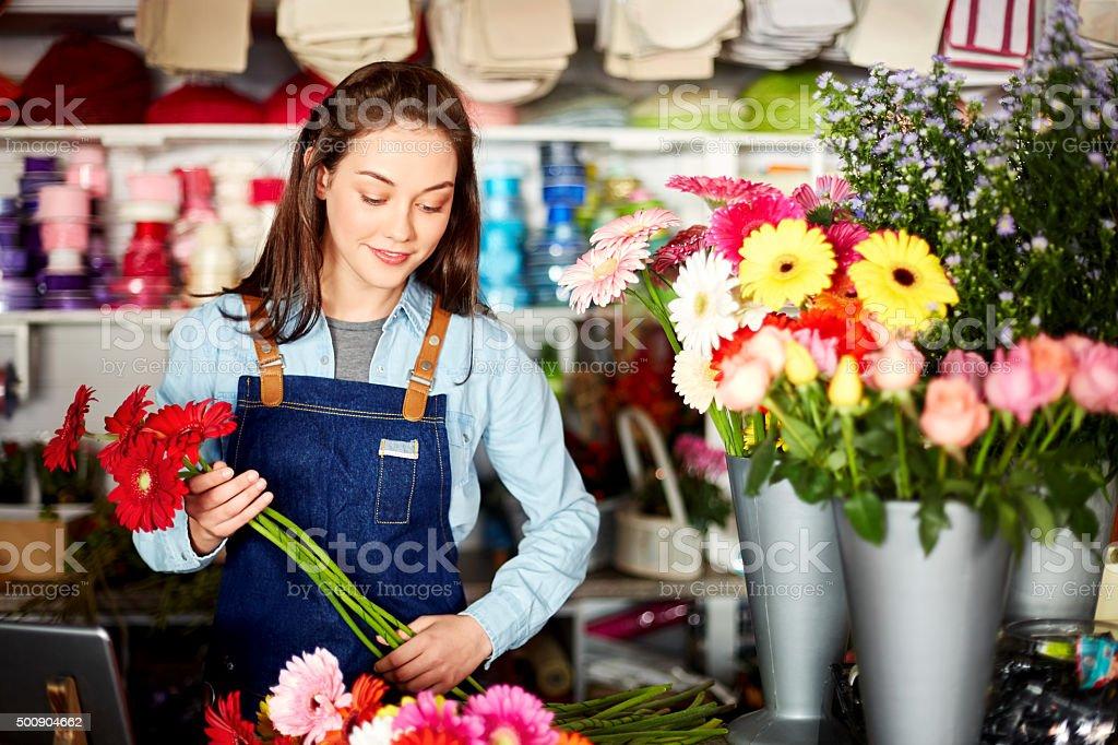Beautiful florist holding fresh Gerbera daisies in flower shop stock photo
