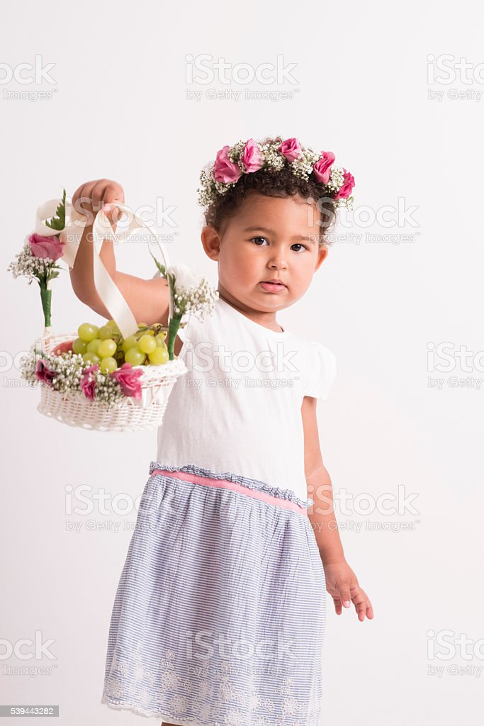 Beautiful flower girl holding basket with fruits. stock photo