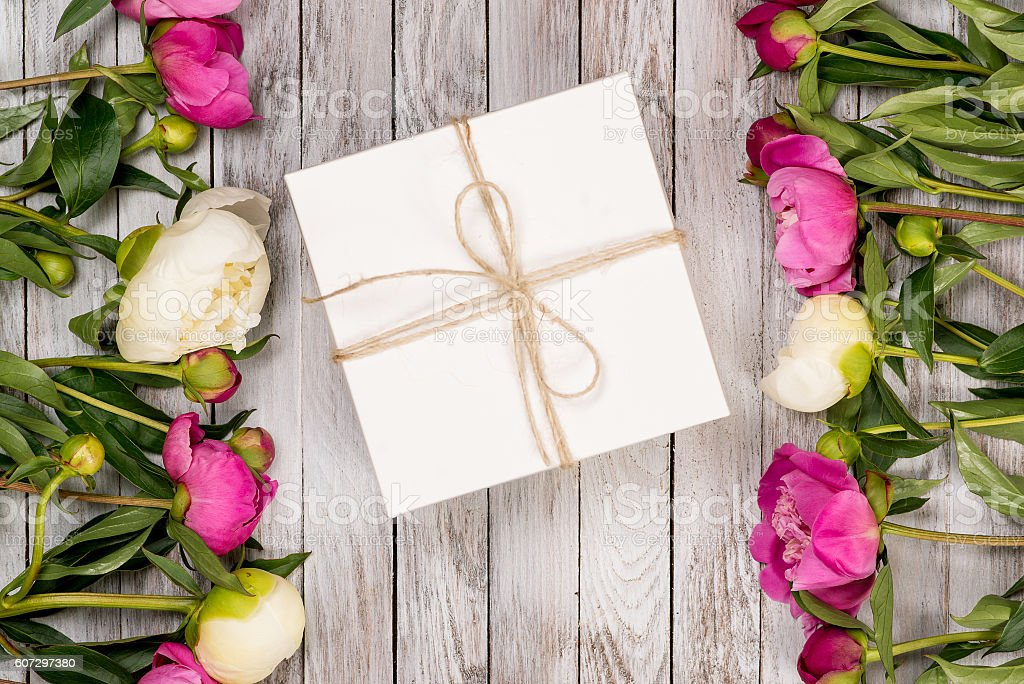 Beautiful flowers peonies with gift box on the light wooden...
