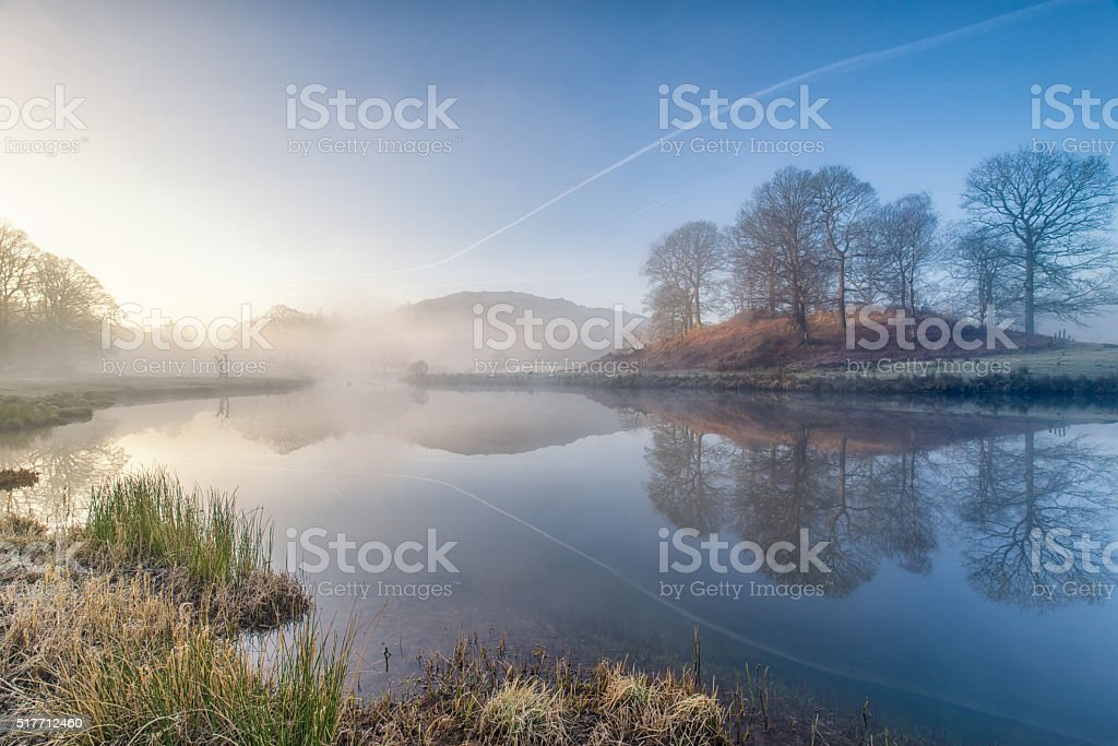 Beautiful foggy dawn river reflections in the Lake District stock photo