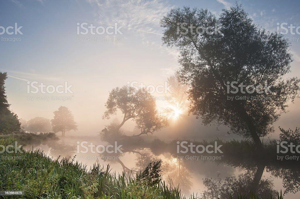 Beautiful foggy sunrise landscape over river stock photo