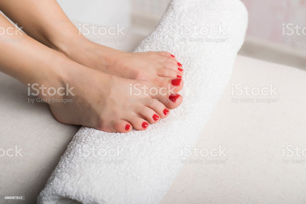 Beautiful foot with gel red pedicure on white towel roll stock photo