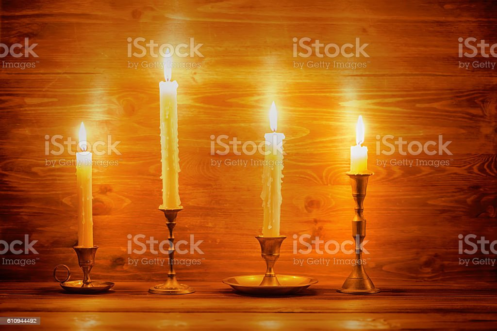beautiful four candles with different vintage candlesticks stock photo