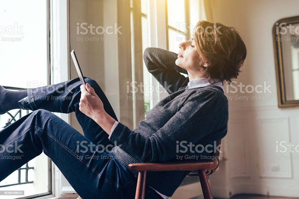 beautiful  french woman relaxing with tablet in Paris apartment stock photo
