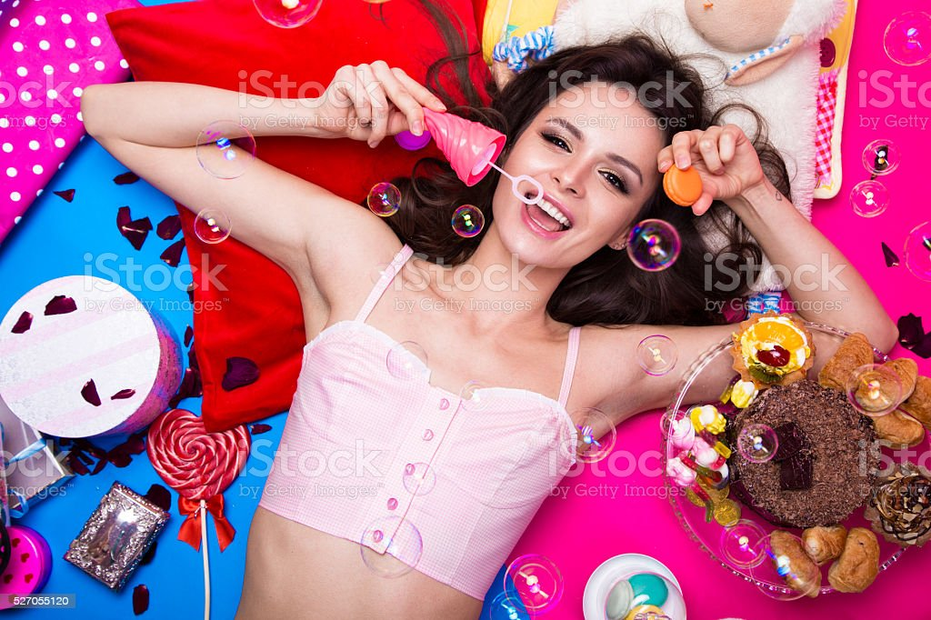 Beautiful fresh girl doll with soap bubbles lying on bright stock photo