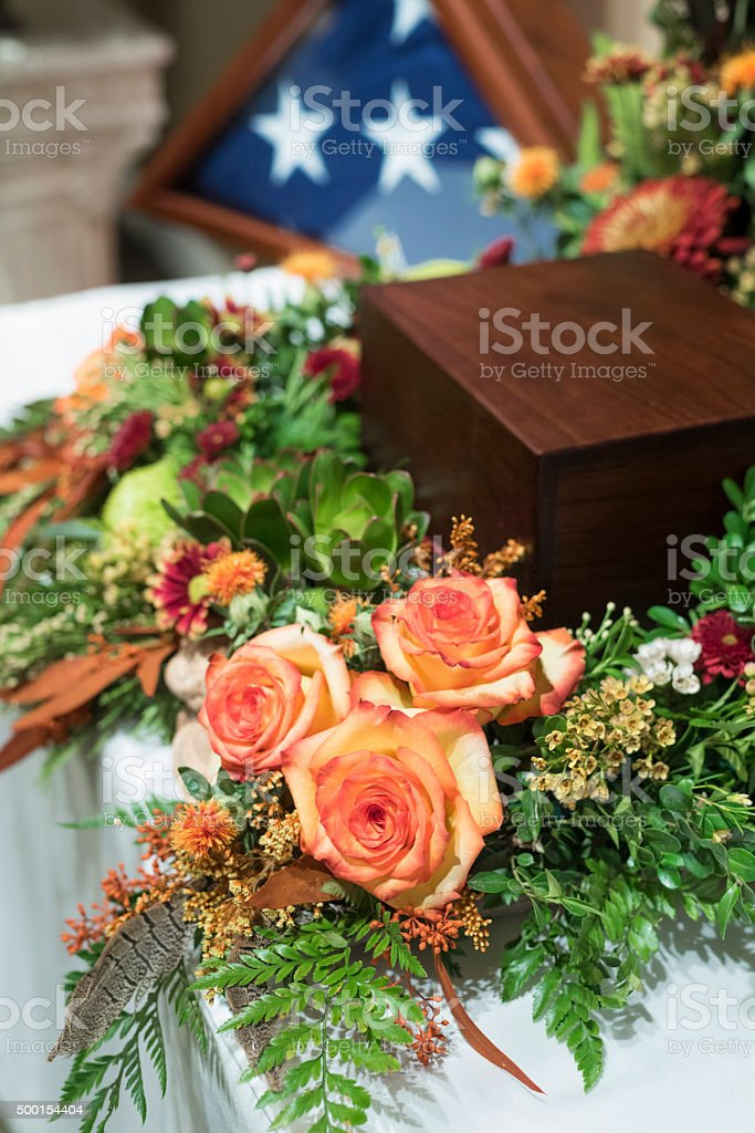 beautiful funeral arrangement with urn and flowers stock photo