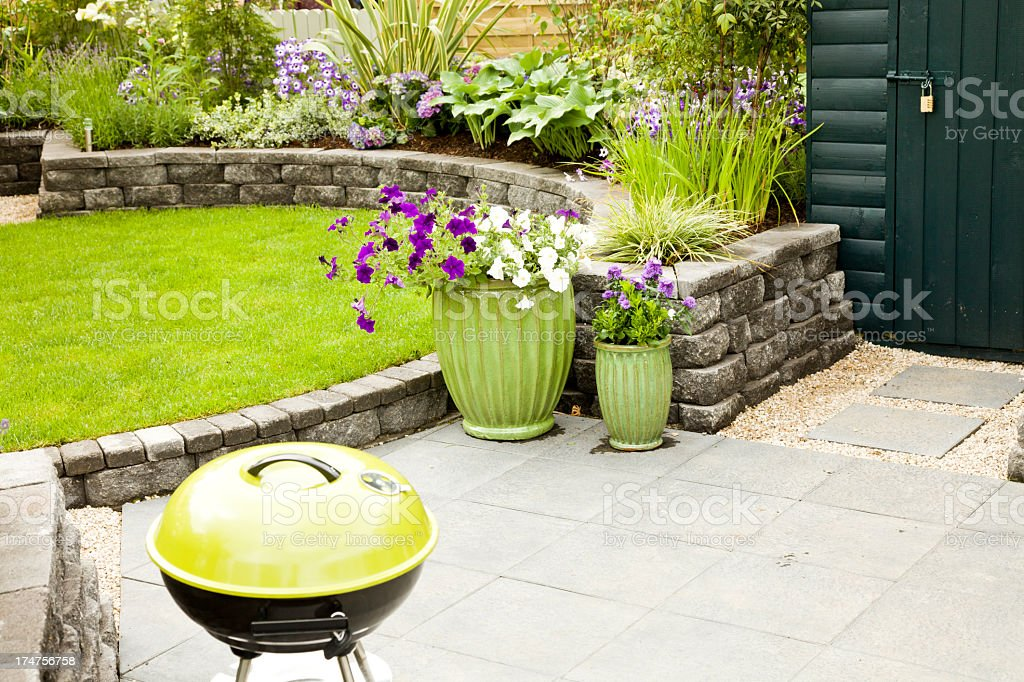 Beautiful garden patio with barbecue and variety of plants stock photo