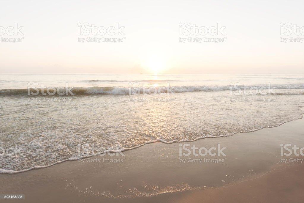 Beautiful gentle surf at beach during sunrise stock photo