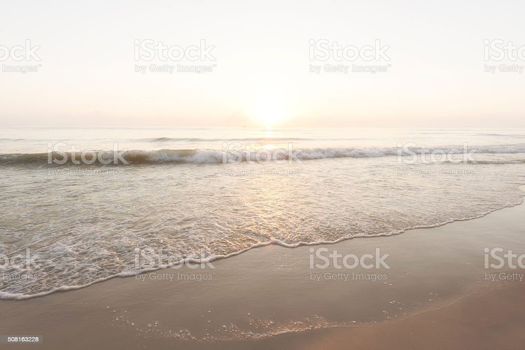 Beautiful gentle surf at beach during sunrise stock photo