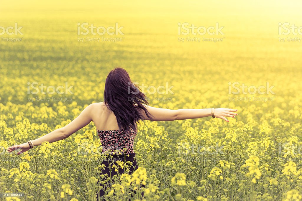Beautiful genuine woman in sunny summer meadow from behind left stock photo
