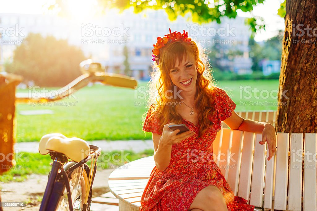 Beautiful ginger smiling after bicycle ride stock photo