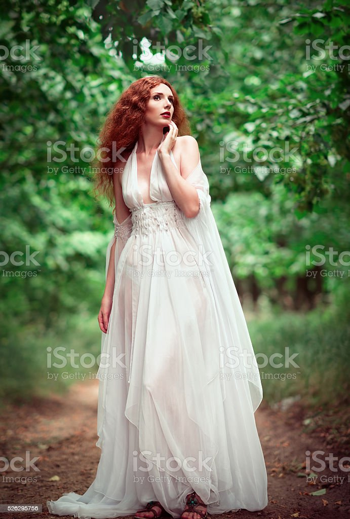 Beautiful ginger woman wearing white dress in a grove stock photo