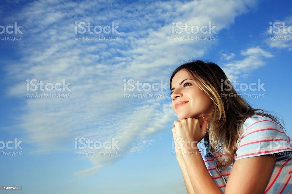 Beautiful girl against blue sky stock photo