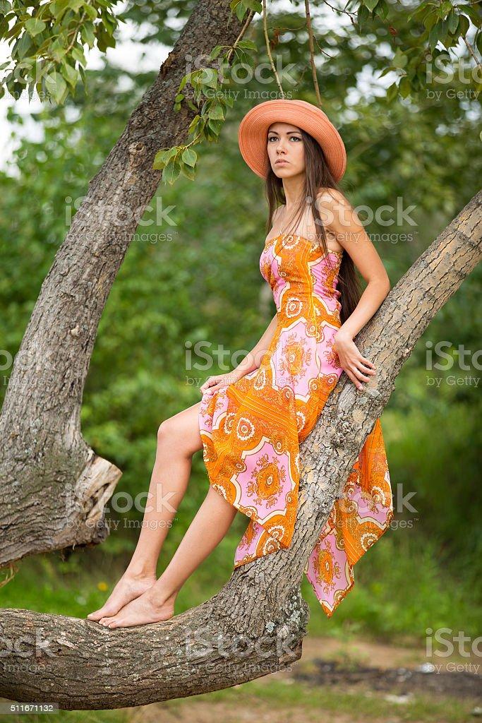 beautiful girl an orange dress and hat sitting on tree stock photo