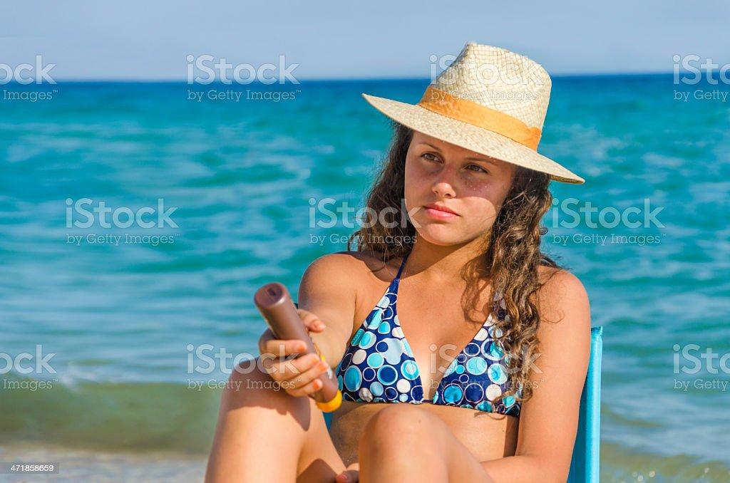 Beautiful girl apply sun protection cream while sunbath. royalty-free stock photo