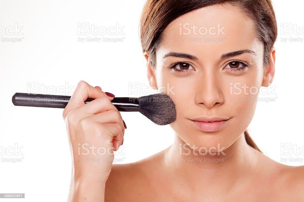 Beautiful girl applying powder on her face stock photo