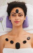 Beautiful girl at stone massage spa in wellness center