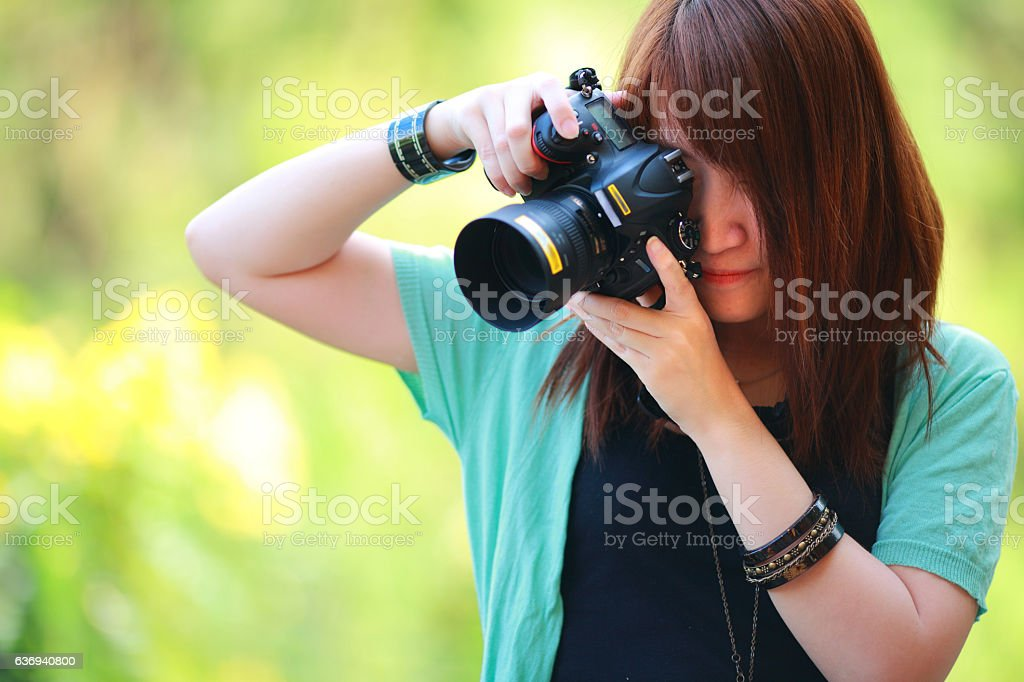 beautiful  girl at summer green park with digital camera. stock photo