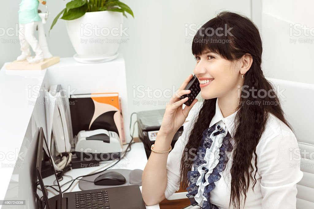 Beautiful girl at the reception answering call stock photo