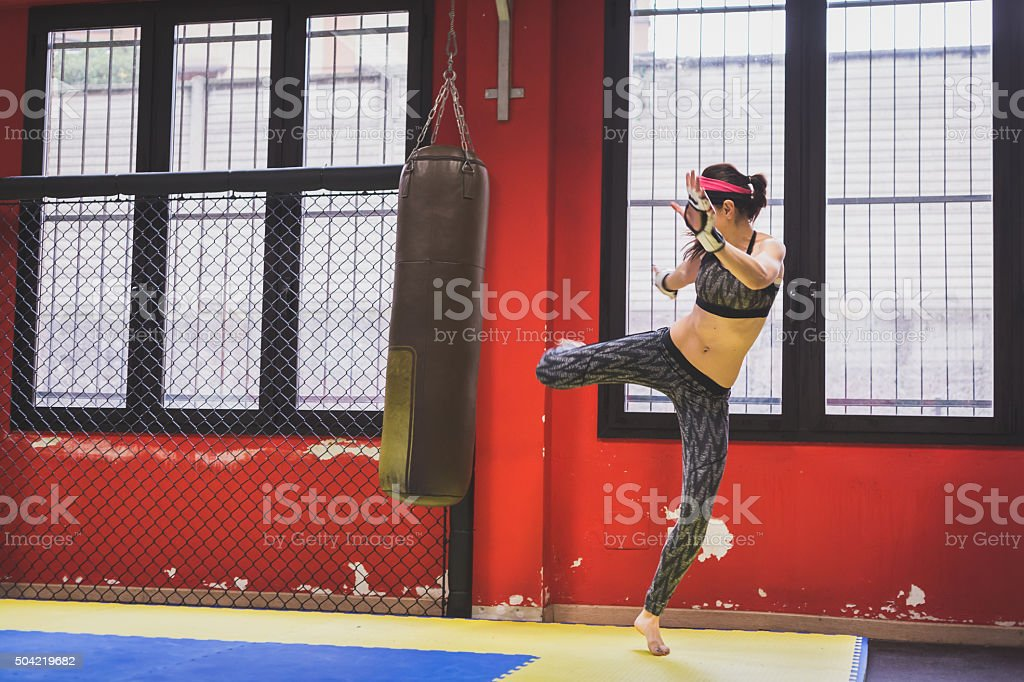 Beautiful girl boxing against punching bag stock photo