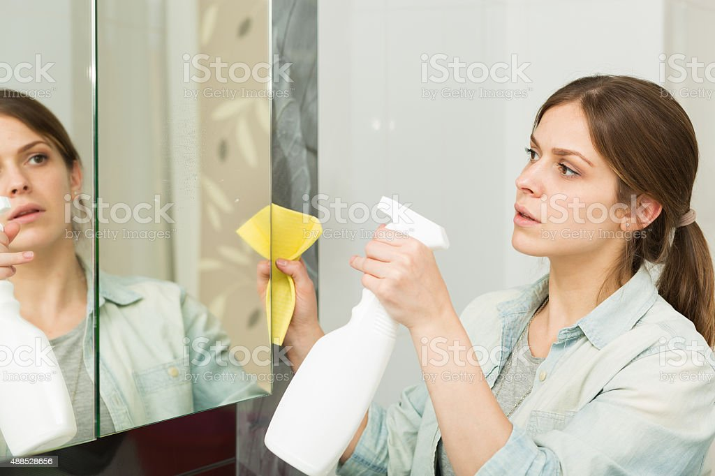 Beautiful girl cleaning up her house stock photo