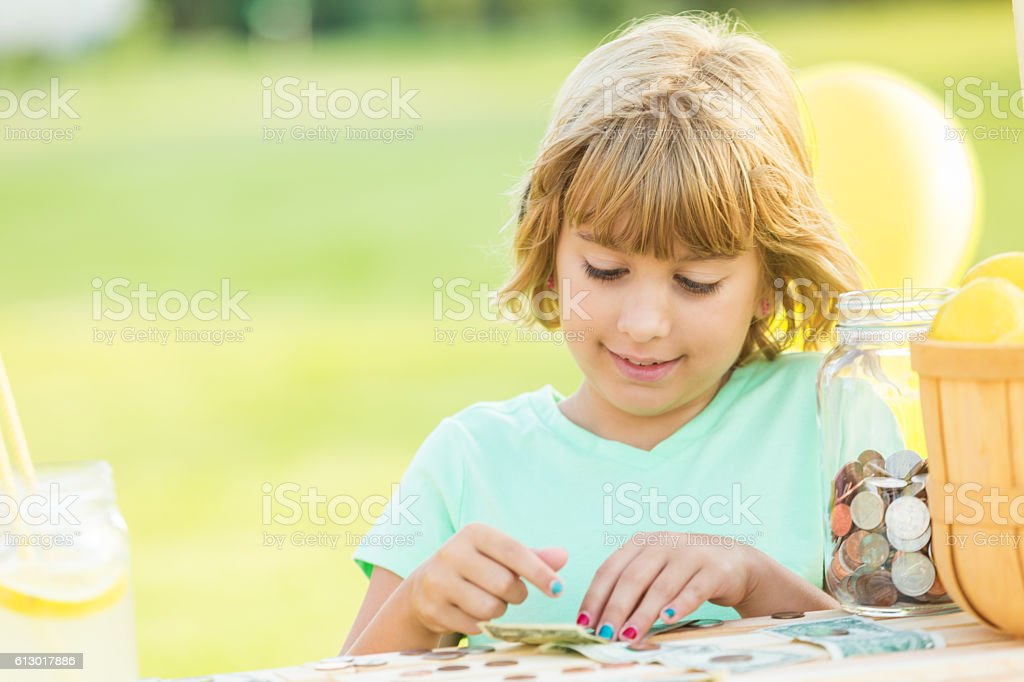 Beautiful girl counts profits received from lemonade stand stock photo