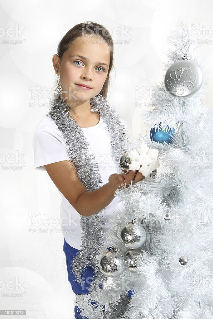 beautiful girl decorates the Christmas tree royalty-free stock photo